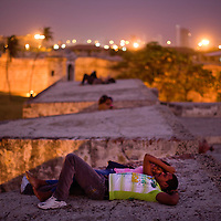 The fortress wall around Cartagena, Colombia was built in the 1600's to protect the affluent Spanish colony from the frequent pirate attacks that plagued the cities. Now it is a hot spot for tourists and locals alike to walk along and becomes especially frequented by lovers for sunset and youth in the evening who drink and enjoy the strong sea breeze. ..Photo by Robert Caplin.
