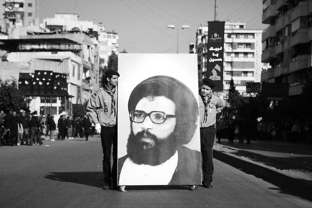 In the procession from the mosque, Scouts wheel a portrait of former Hezbollah leader Abbas al-Mussawi.