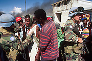 12 FEBRUARY 1996, PORT AU PRINCE, HAITI: US peacekeeping soldiers assigned to the UN mission in Haiti help a Haitian man injured in a melee on the street in the port area of Port au Prince, Haiti, February, 1996..PHOTO BY JACK KURTZ