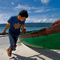 Two men haul a canoe onto the beach on a small island in Central Sulawesi