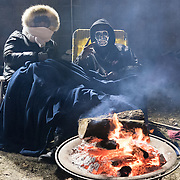 Protestors with the Black Lives Matter movement, including Shaye Charles, left, huddle around fires as they gather for a night of community and protest outside the Minneapolis Police Department 4th precinct headquarters on Thursday, November 19, 2015 in Minneapolis, Minnesota. <br /> <br /> A more mellow and festive atmosphere, with a smaller police presence, prevailed after Wednesday evening's tear gas clashes between police and protesters. <br /> <br /> Protests and an encampment at the site have been ongoing since the police shooting of 24-year-old Jamar Clark by Minneapolis Police on Sunday, November 15. <br /> <br /> <br /> Photo by Angela Jimenez for Minnesota Public Radio www.angelajimenezphotography.com