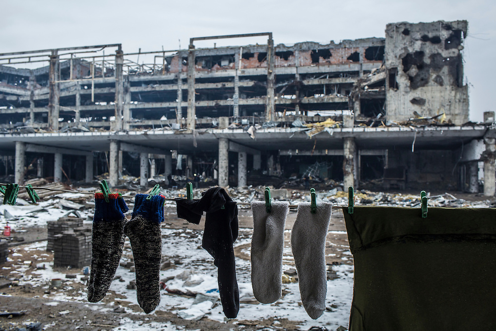 Laundry hangs to dry in a living area for Russian-backed rebels stationed in a parking garage with a view of the destroyed terminal of the Donetsk Airport on Tuesday, March 22, 2016 in Donetsk, Ukraine.