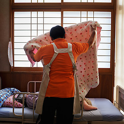 A caretaker helps a patient inside a rest home. Though Ogimi is known for it's active seniors, rest homes for the elderly are still available for those who need them.