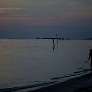 CAPE CHARLES, VA - JUNE 20: A man hunts for crabs as the sun sets over the Chesapeake Bay on Friday, June 20th, 2014 near Cape Charles, Va. (Photo by Jay Westcott/For The Washington Post)