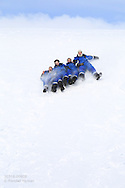 Snowmobilers slide down hill in April between Longyearbyen and Barentsburg; Svalbard, Norway.