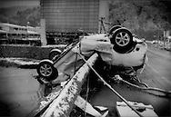 A car has been bent and deposited on the rail of high bridge submerged in the tsunami waters at Kamaishi, Iwate Prefecture, Japan.  The building in the background, despite being atop an embankment had tsunami waters reach the second storey.