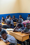 Pupils sit in a classroom at a public school on July 7, 2010 in Port-au-Prince, Haiti. Most schools in Port-au-Prince didn't open until April, three months after the earthquake.