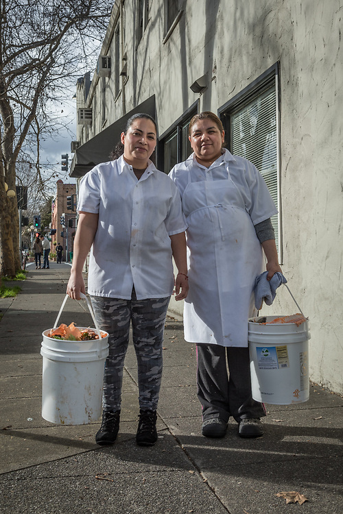 Hydro Grill employees Frances Reyez and Maria Morano carry buckets to the recycling bin in downtown Calistoga