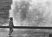Bundled against the windy weather, a stroller along Beach Drive Southwest near Alki ignores the waves breaking against the retaining wall. The forecast called for more windy, rainy weather, and mild temperatures were expected to continue through that week. (Cole Porter / The Seattle Times, 1984)