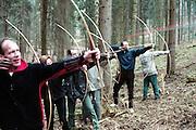 """Bogenschützen schiessen im Wald bei Hitzacker Pfeile auf ein Ziel ab. Beim """"instinktiven Bogenschiessen"""" benutzen die Sportler keine Hightech-Bogen mit Zielhilfen. traditional archery, flying arrow."""