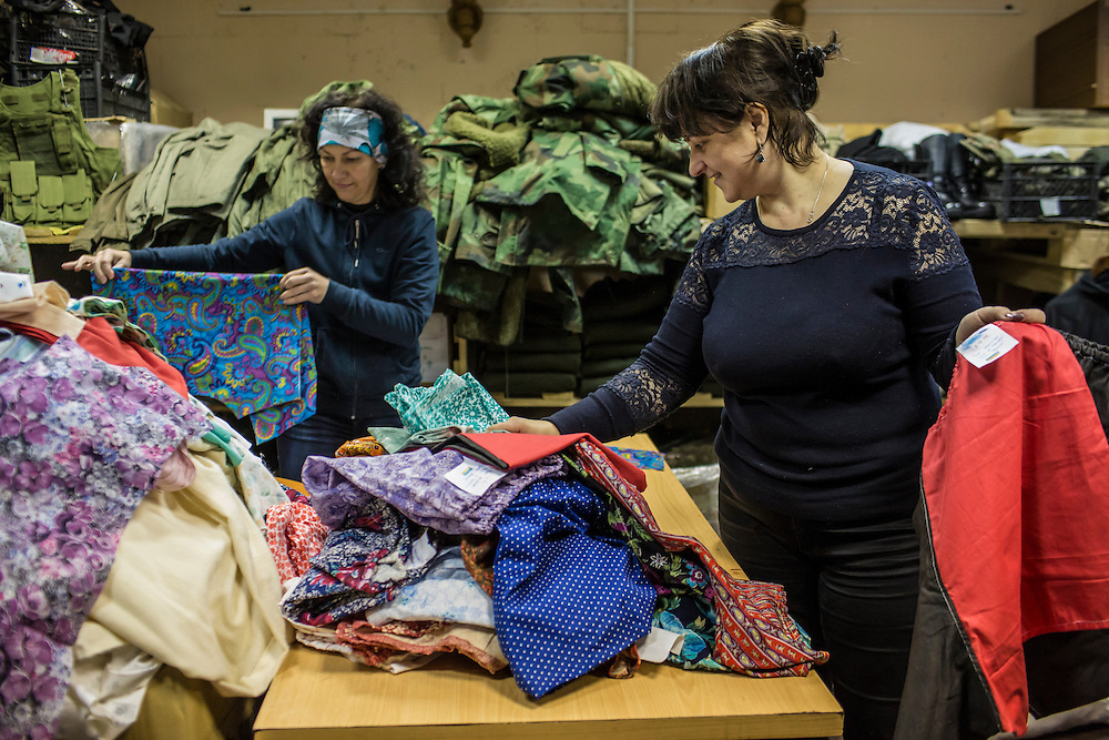 DNIPROPETROVSK, UKRAINE - NOVEMBER 16, 2014:  Lyudmyla Makaida, 48, a designer, left, and Tanya Volynets, 46, a lawyer, right, with underwear they've made for soldiers at the Dnipropetrovsk Volunteer Logistics Center, a charity organization that produces supplies for pro-Ukrainian fighters battling rebels in the country's East, in Dnipropetrovsk, Ukraine. CREDIT: Brendan Hoffman for The New York Times