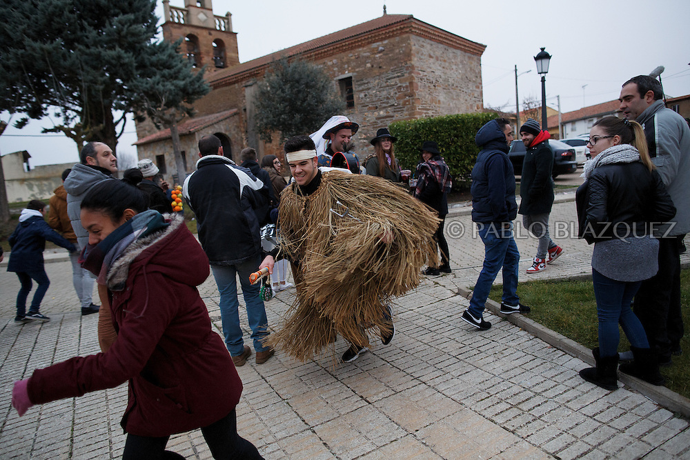 A man dressed as El Tafarron chases a reveller during El Tafarron festival on December 26, 2016 in Pozuelo de Tabara, Zamora province, Spain.  El tafarron is a pagan winter masquerade that takes place during Saint Esteban festivities. The festival is represented by El Tafarron and La Madama. El wears a custome of straw and a mask. (© Pablo Blazquez)