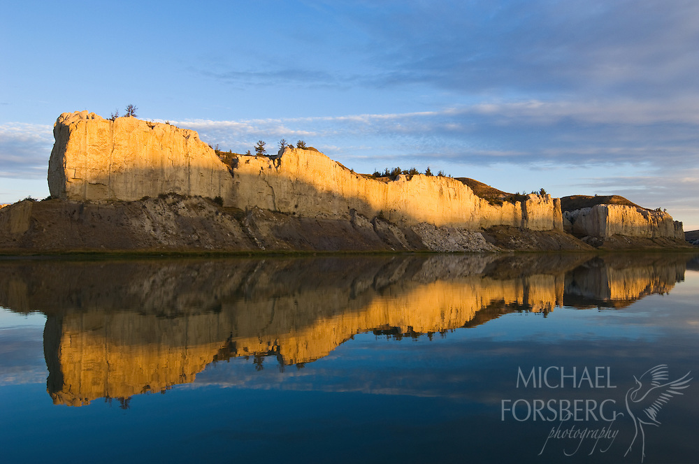 The white cliffs of the Upper Missouri River Breaks National Monument are reflected in a calm Missouri River.  Montana.