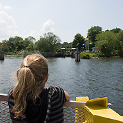 A young girl looks over the Connecticut River as the ferry on which she is riding approaches the terminal in Haddam, Connecticut.