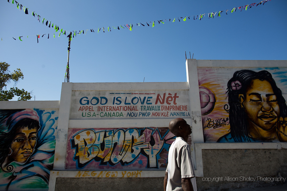 A man walks past the site of the collapsed Notre dame du Perpetuel Secours Catholic church in the Bel Air neighborhood of Port-au-Prince, Haiti, January 3, 2015.  A temporary church was constructed just behind the wall.