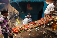 Grieving man gets his head shaved while a dead body is carried for cremation in a bamboo stretcher swathed in cloth at Manikarnika Ghat, by the Ganges river, in Varanasi, India.