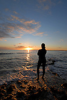 Young woman enjoying a beautiful sunset at Migjorn beach, Formentera