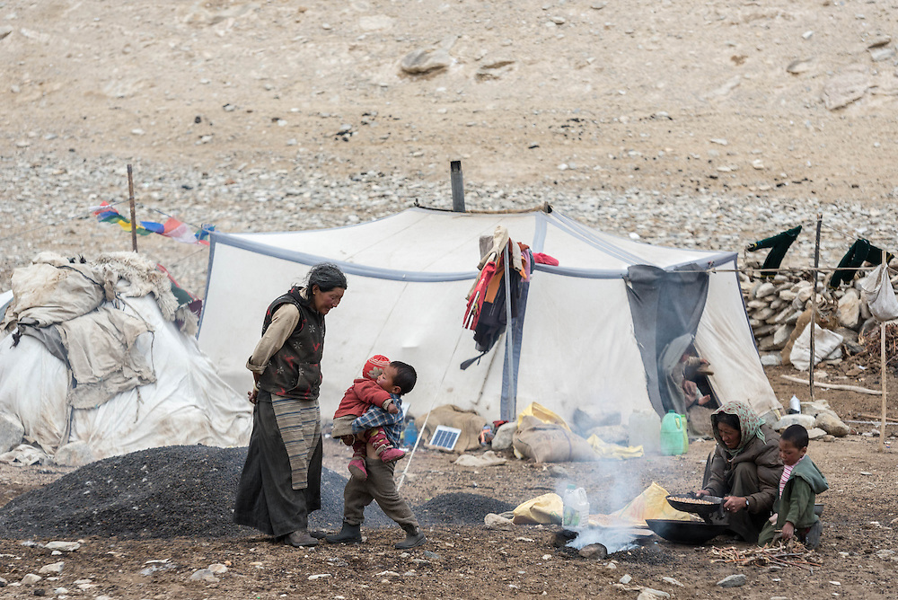 A Tibetan family outside their tent in the village of Puga on Ladakh's Changtang plateau. The woman by the fire is roasting barley.