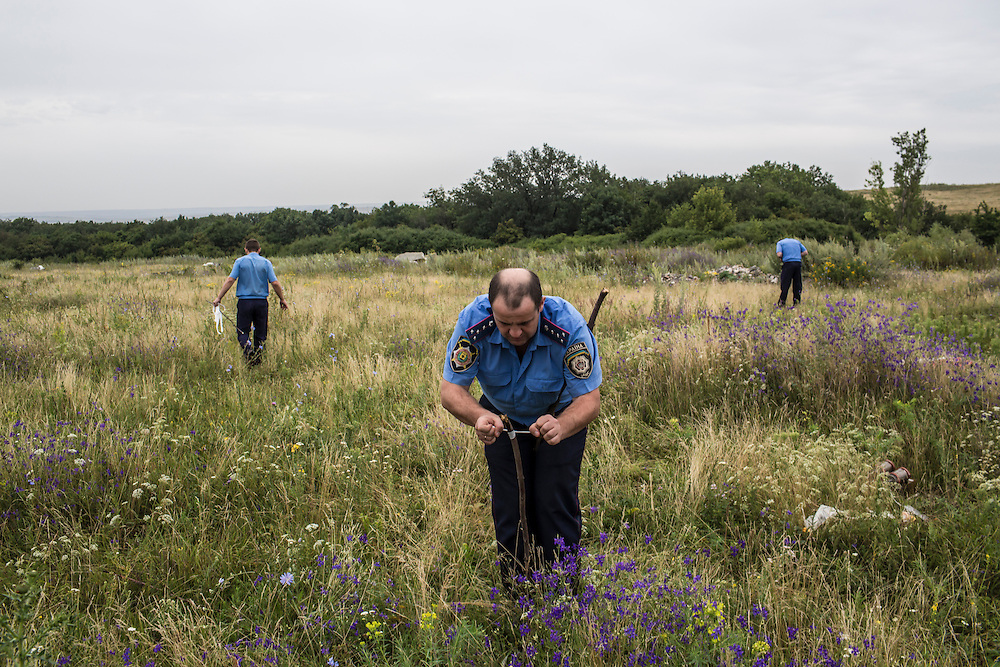 GRABOVO, UKRAINE - JULY 18: A Ukrainian police officer ties a white ribbon to a stake to mark human remains found in a field after a commercial passenger plane was shot from the sky by a missile the previous day on July 18, 2014 in Grabovo, Ukraine. Malaysia Airlines flight MH17 travelling from Amsterdam to Kuala Lumpur has crashed on the Ukraine/Russia border near the town of Shaktersk. The Boeing 777 was carrying 280 passengers and 15 crew members. (Photo by Brendan Hoffman/Getty Images) *** Local Caption ***