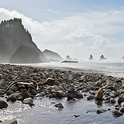 Pacific Ocean waves have eroded seastack rocks from high bluffs and created a rocky beach, south of Cape Meares on the Oregon coast, USA. Puffy clouds roll across the blue sky. Panorama stitched from 2 overlapping images.