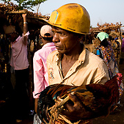 A mine worker carries home a chicken from the Sunday market in the Sundergarh distrct. Sundergarh, Orissa, India.