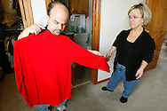 Chris Kotzian (L) looks at a shirt for fit with wife Barb at their home in Thornton, Colorado March 25, 2010.  Both about four-feet-tall,  the Kotzians are both achondroplasia dwarfs, a rare genetic disorder of bone growth and have to have nearly all their clothes altered to fit.  Preferring to be called little persons they both are active in the Little People of America, the only dwarfism support organization that includes all 200+ forms of dwarfism.  REUTERS/Rick Wilking (UNITED STATES)