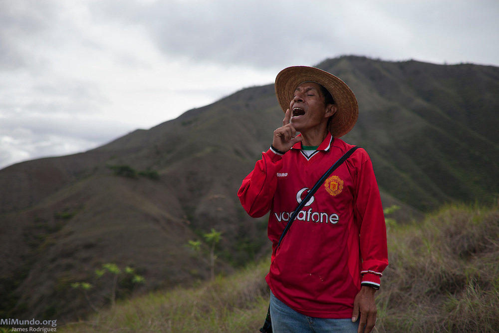 Massacre survivor Sebastian Iboy Osorio calls out to a neighbor across the Chixoy Dam reservoir. Iboy Osorio, originally from the community of Rio Negro, survived the four massacres carried out by the Guatemalan army and civil patrolmen from neighboring Xococ against residents of Rio Negro in 1981 and 1982. Nearly 400 community members of Rio Negro were killed due to the community's resistance to give up their lands and make way for the Chixoy hydroelectric project. Rio Negro, Rabinal, Baja Verapaz, Guatemala. May 17, 2014.