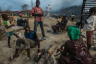 LACADONIE, HAITI - OCTOBER 10, 2016: Kettle Nazaire, 23 cooks a rotting, putrid-smelling goat leg from an animal that had died a week earlier and during Hurricane Matthew. The storm killed several villagers and most of the community's livestock…in addition to destroying all homes and crops. Now, villagers dedicate their days to the busy work of staving off starvation. Mrs. Nazaire took oranges plucked from the ground and squeezed them over the meat in effort to make it taste less sour - which stuck to a rustic cutting board fashioned from a log in pink smears.  PHOTO: Meridith Kohut for The New York Times