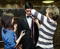 IRVINE, CA - MARCH 2:  Student Jeffrey Garcia gets finishing touches after getting fitted with tuxedos donated by the Mens Wearhouse (www.menswearhouse.com) at the Working Wardrobes Dream Girls & Distinguished Gentlemen 2013 event at the Irvine Hilton in Irvine, CA. Working Wardrobes (http://www.workingwardrobes.org) is a non-profit organization located in Costa Mesa, CA. PHOTO: © 2013 SILVEX.PHOTOSHELTER.COM.