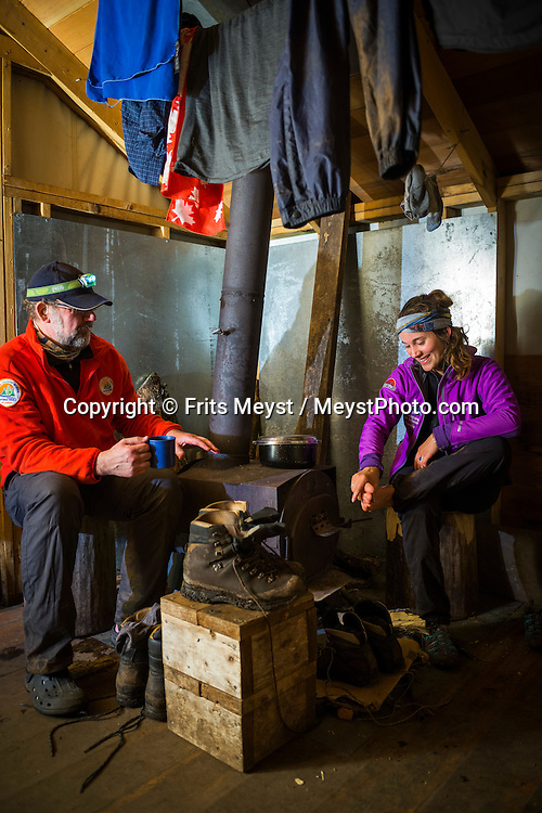 Alaska, USA to Yukon Territory, Canada, September 2014. hikers drying their cloths and warm up at the wood stove in Sheep Camp. Hiking from Finnigan's Point to Sheep Camp through thick Pacific rainforest. Starting at Dyea, Alaska, The Chilkoot Trail retraces the Klondike Gold Rush route that most stampeders followed to get to the gold fields. Steeped in Klondike Gold Rush history and scattered with relics from the past, the famous Chilkoot Trail is also referred to as the longest open air museum in the world. This rugged 55 kilometer wilderness trek is a world-renowned hiking trail and Canada's largest National Historic Site. Photo by Frits Meyst / MeystPhoto.com