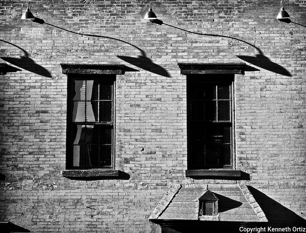 A late day shot of two windows and shadows streaming across them.
