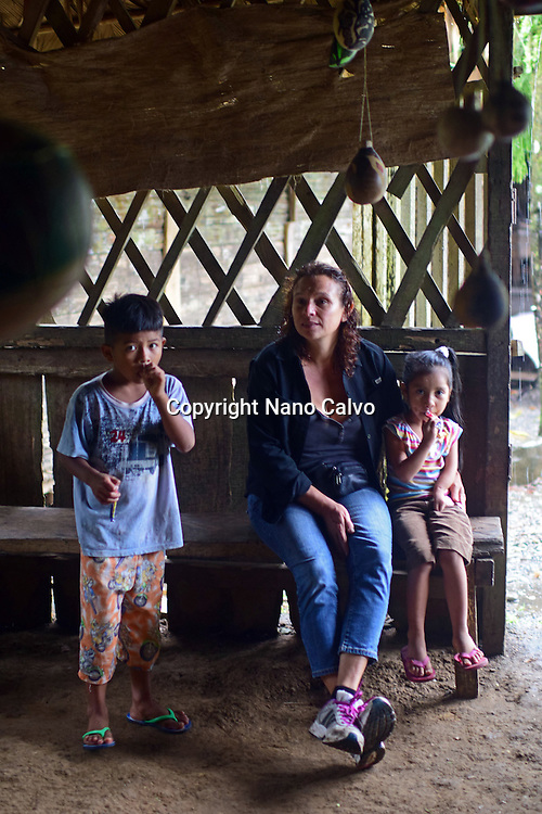 Karine, the guide, watching the rain with two Bribri kids, Dereck and Karen. <br /> <br /> A day with the Bribri, indigenous people in Lim&oacute;n Province of Costa Rica