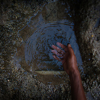 A man reaches into a pothole with a broken water line to retreive water to brush his teeth in Mumbai, India.