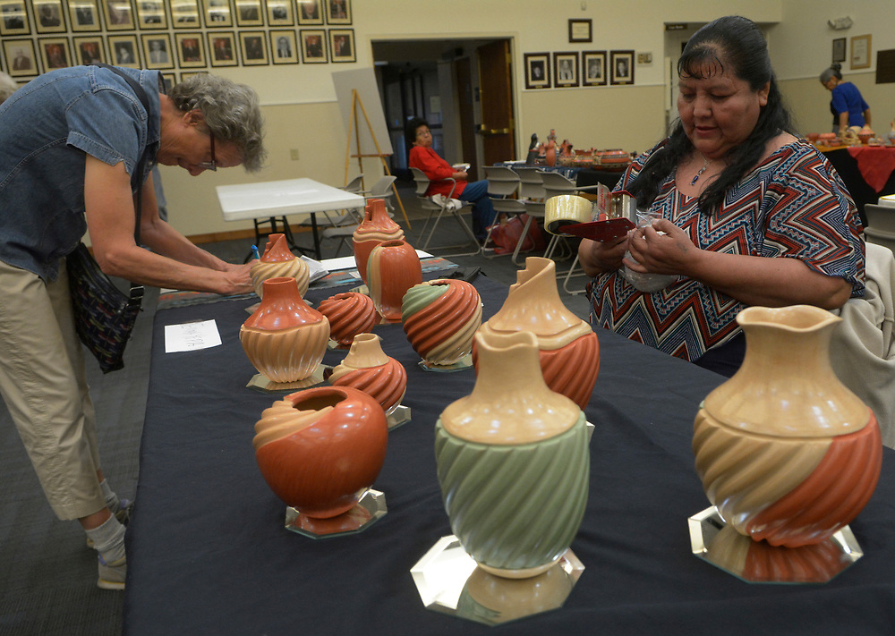 gbs031917b/ASEC -- As Judy Yandoh of Albuquerque, left, writes a check, artist Emma Yepa of Jemez Pueblo wraps a piece of her pottery at the Jemez Pueblo Artisan Fair at Congregation Albert on Sunday, March 19, 2017. This was Congregation Albert Bortherhood's 2nd Annual Jemez Pueblo Artisan Fair in conduction with the Jemez Arts and Crafts Association.