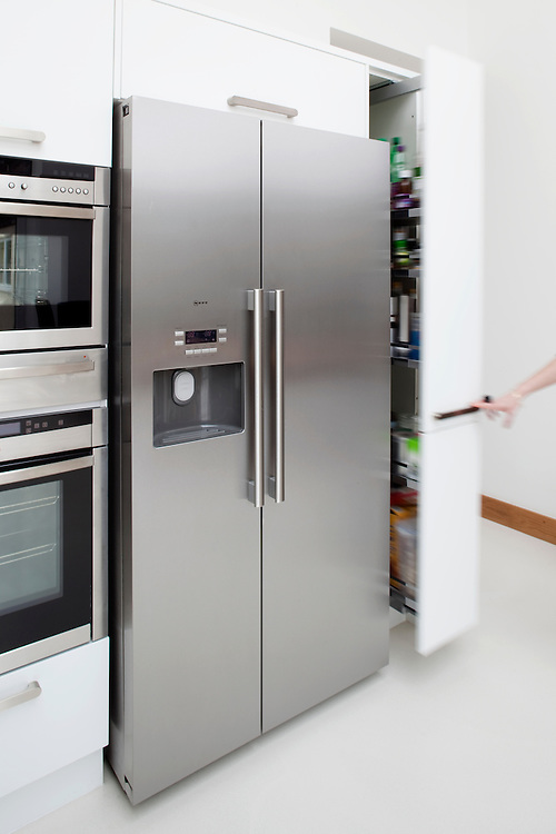 kitchen cupboard opening with blurred arm next to a fridge freezer unit by NEF Kitchen interiors