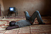 a young african migrant watching television inside a ghetto in Agadez