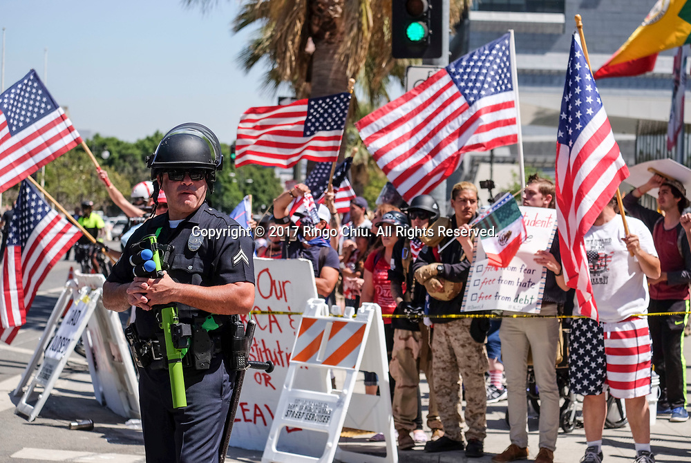 A group of President Donald Trump supporters in background and May Day protesters taunt each other as they are separated by police officers during the annual May Day March in Los Angeles, May 1, 2017. (Photo by Ringo Chiu/PHOTOFORMULA.com)<br /> <br /> Usage Notes: This content is intended for editorial use only. For other uses, additional clearances may be required.