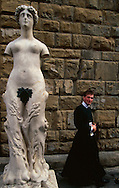 A priest walks by a statue in Piazza della Signoria in Florence.