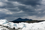 Rain clouds and the Talkeetna Mountains contrast with bright sun on Matanuska Glacier in Southcentral Alaska. Summer. Afternoon.