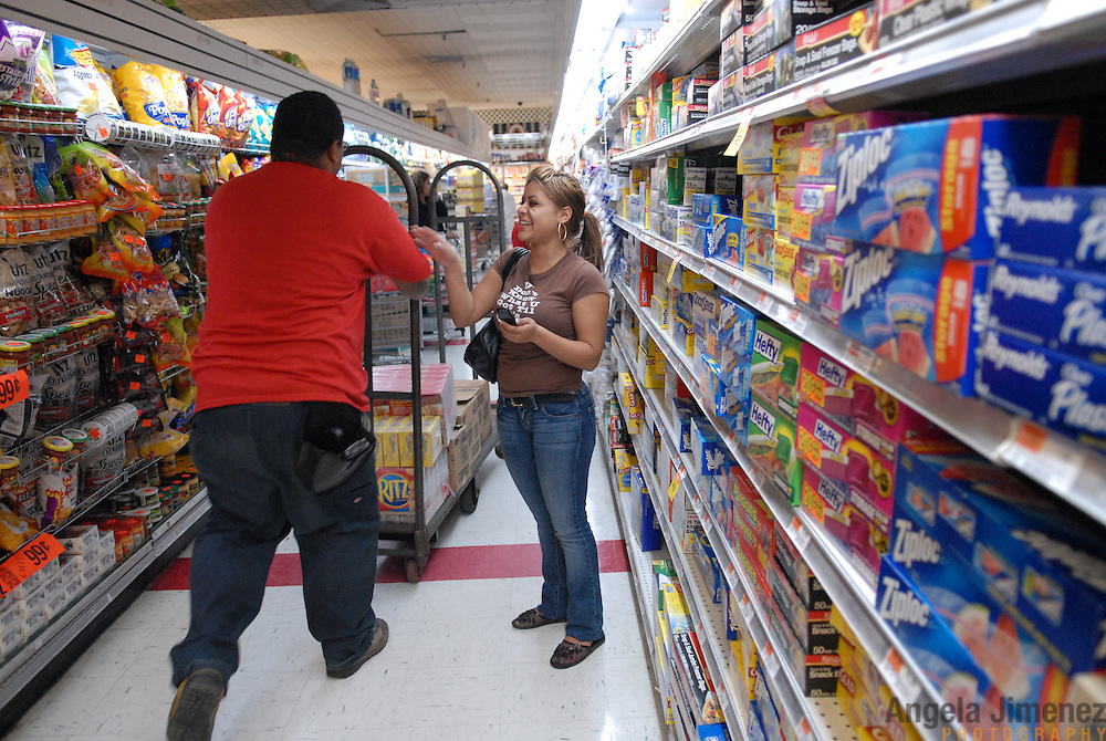 DATE: 6/7/07<br /> DESK: CTY<br /> SLUG: CTOWN<br /> ASSIGN ID: 30044113A<br /> <br /> Cashier Luzmarie Rolon, right, jokes with a stockboy as he walks by during a break from her shift at Steve's C-Town, a grocery store on 9th Street between 5th and 6th Avenues in Park Slope, Brooklyn on June 7, 2007. <br /> <br /> photo by Angela Jimenez for The New York Times<br /> photographer contact 917-586-0916
