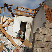Raymond Butler tries to open a door as he shows contractors damage in his home, a result of the tornado that touched down the night before in Rice, Texas, October 25, 2010.  (Courtney Perry/The Dallas Morning News)