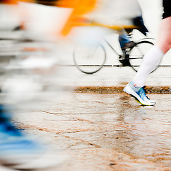 Intentionally motion blurred abstract image of runners and a person cycling. Low angle view