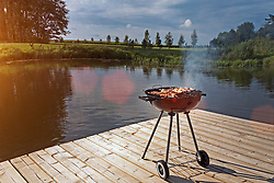 Barbecue grill on wooden platform  by lake in Estonia
