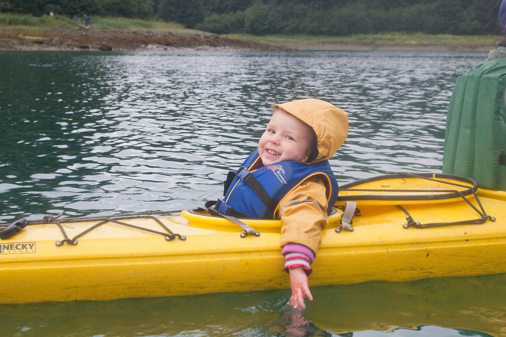 A happy girl tests the waters from her kayak in Glacier Bay National Park. MR MRA