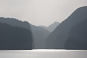 Misty silhouette of limestone karsts and islands in Ha Long Bay, near Cat Ba Island, Vietnam