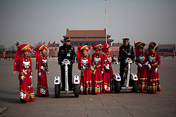 Stewardesses in ethnic minority costumes pose with police on self balanceing electric vehicles in Tiananmen Square before the opening session of the National Peoples Congress (NPC) in the Great Hall of the People in Beijing, China, on 05 March 2011. The NPC has over 3,000 delegates and is the world's largest parliament or legislative assembly though its function is largely as a formal seal of approval for the policies fixed by the leaders of the Chinese Communist Party.