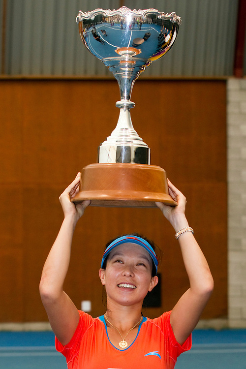 China's Zheng Jie  with the trophy after defeating Italy's Flavia Pennetta, who retired injured, in the singles final at the ASB Classic Women's Tennis Tournament, Auckland, New Zealand,  Sunday, January 08, 2012.  Credit:SNPA / David Rowland