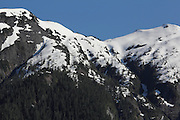 Snow still covers some mountains along Canada's Inside Passage in early June, seen from the ferry between Port Hardy in Vancouver Island to Prince Rupert
