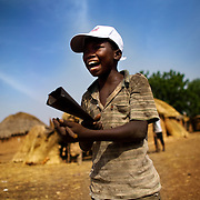 A boy uses a traditional musical instrument to announce an upcoming national polio vaccination exercise in the village of Gbulahabila, northern Ghana on Wednesday March 25, 2009.