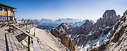 "From Rifugio Guido Lorenzi on Monte Cristallo in the Ampezzo Dolomites, look northeast across blue ridges of the Sesto Dolomites (Dolomiti di Sesto, or Sexten/Sextner/Sextener Dolomiten) to the pyramids of Tre Cime di Lavaredo (Italian for ""Three Peaks of Lavaredo,"" called Drei Zinnen or ""Three Merlons"" in German). A lift to Forcella Staunies on Monte Cristallo gives unforgettable views over the Dolomites mountains (part of the Southern Limestone Alps) near Cortina d'Ampezzo, in the Province of Belluno, Veneto region, Italy, Europe. Monte Cristallo lies within Parco Naturale delle Dolomiti d'Ampezzo. Directions: From Cortina, drive 6km east on SR48 to the large parking lot for Ski Area Faloria Cristallo Mietres (just west of Passo Tre Croci Federavecchia). Take a chair-lift from Rio Gere to Son Forca (rising from 1698m to 2215m). Then take the old style ovovia (egg-shaped) Gondellift Forcella Staunies to Rifugio Guido Lorenzi (2932m) for astounding views. Climbers enjoy spectacular via ferrata routes here. Cortina gained worldwide fame after hosting the 1956 Winter Olympics. UNESCO honored the Dolomites as a natural World Heritage Site in 2009. This panorama was stitched from 8 overlapping photos."